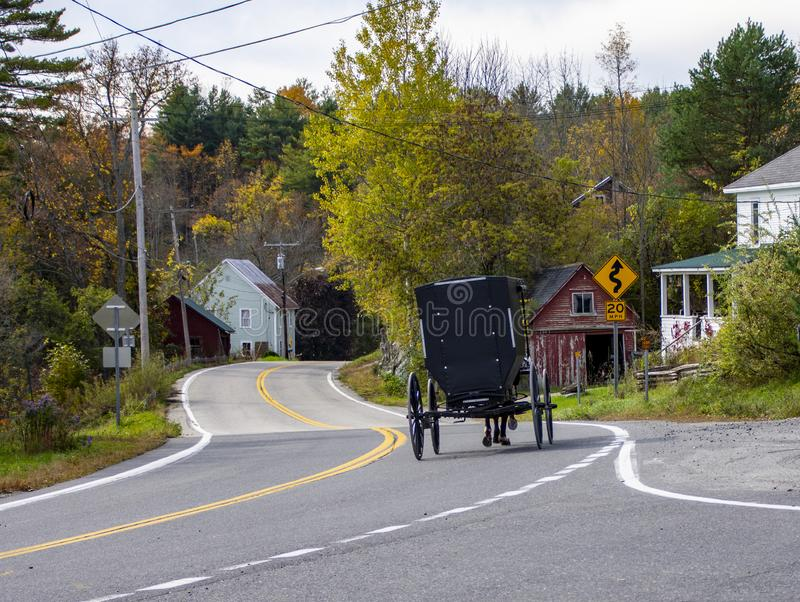 The back of an Amish Carriage in Upper New York State during Autumn. An Amish couple riding through a small town in Upper New York State during the New England royalty free stock image