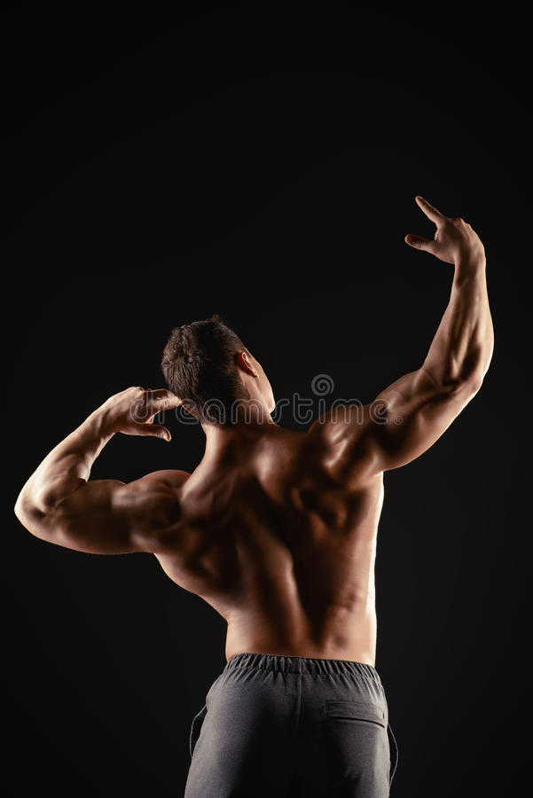 Back and arms. Athlete bodybuilder man demonstrating his perfect muscular body - muscles of the back and arms. Over black background stock image