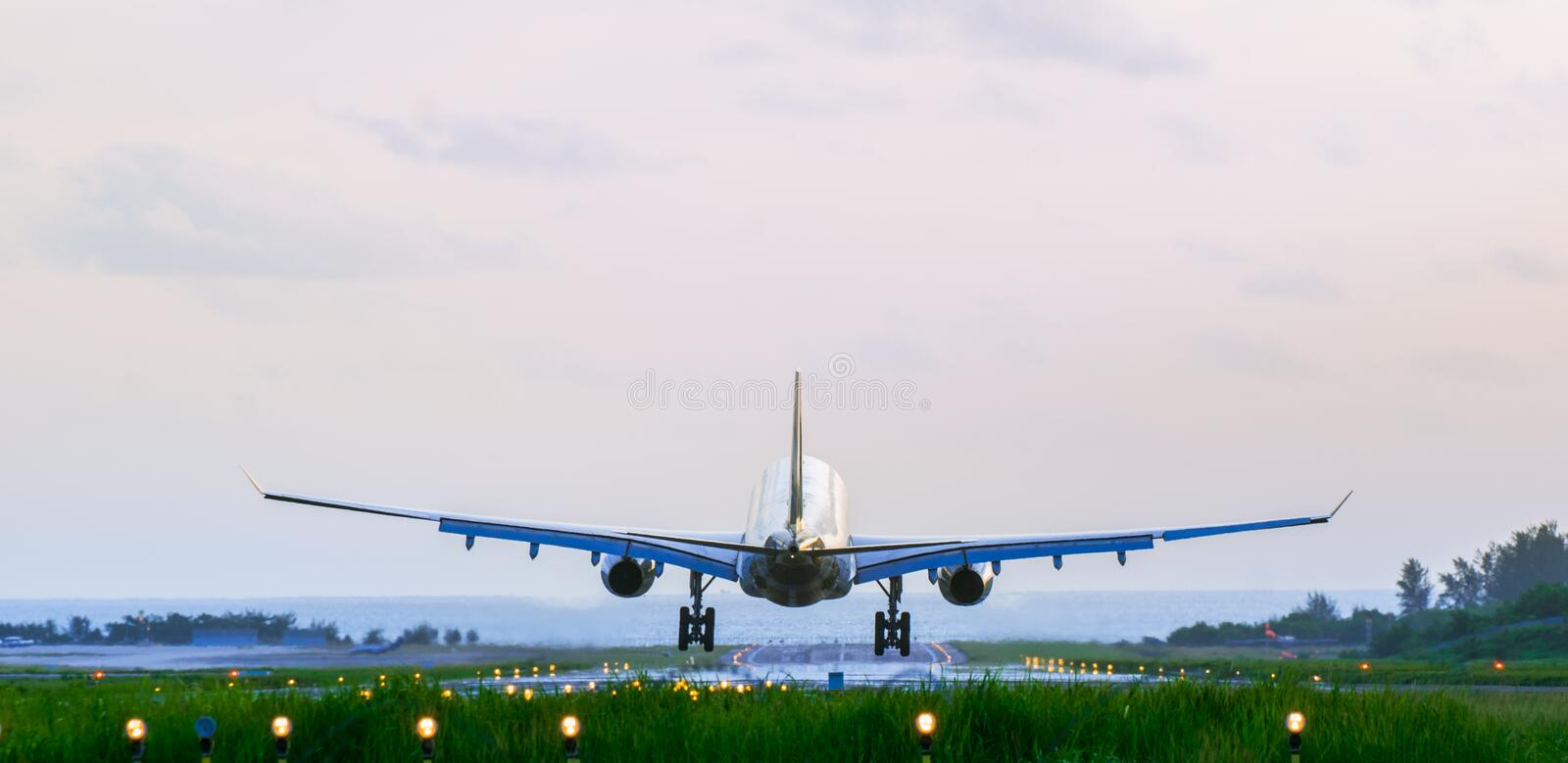 Back of the arriving airplane stock photos