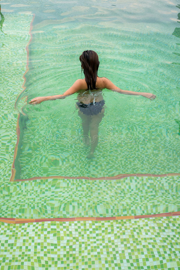 Back of Asian girl walking and relaxing in the swimming pool royalty free stock photos
