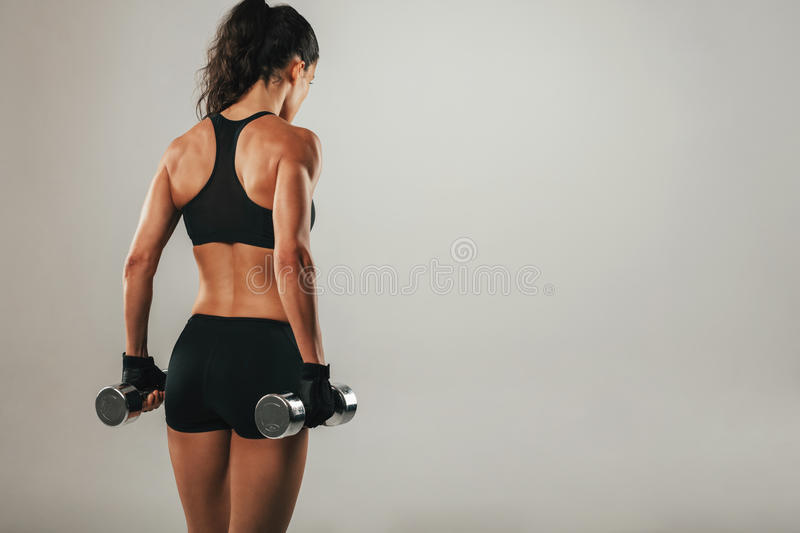 Back of athletic woman holding weights. Back of athletic woman with muscular physique holding pair of chrome finished dumbbells over gray background with copy stock image