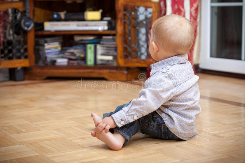 Back of baby boy child kid indoor. At home. Happy childhood. Full length of baby boy sitting on the floor. Back of child kid. Indoor. At home stock photo