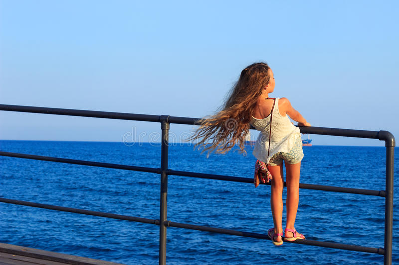 Back beautiful little Teen Girl with long flowing curly hair in stock image