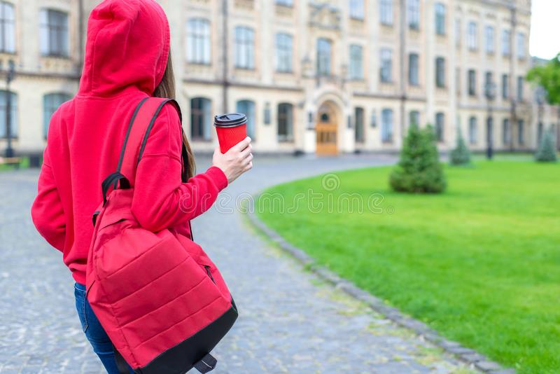 Back behind rear view photo of satisfied nice hipster person enjoying tea going to the building royalty free stock image
