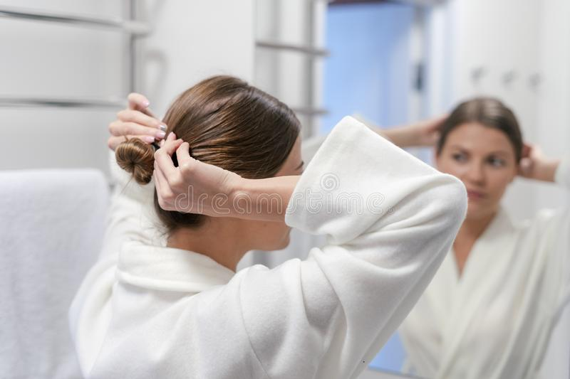 Woman in white bathrobe looking at mirror in bathroom. Back behind rear view of woman in white bathrobe  standing near mirror in bathroom, making hairdo royalty free stock images