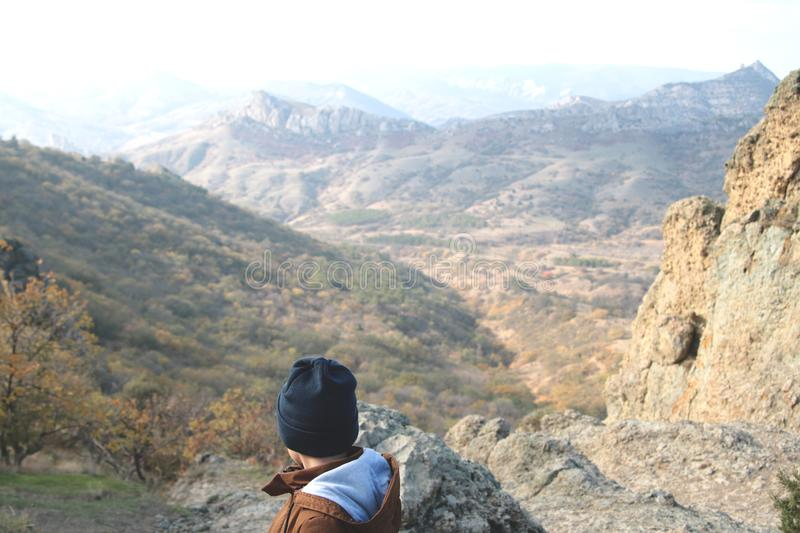 A boy standing above the mountain range. royalty free stock images
