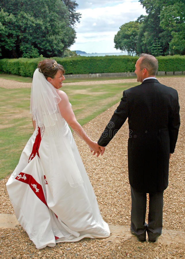 Back of Bride and Groom Holding Hands stock photo