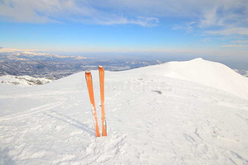 Back country ski. Pair of back country ski with orange climbing skin or sealskin on the summit with superb view of the valleys below stock photo