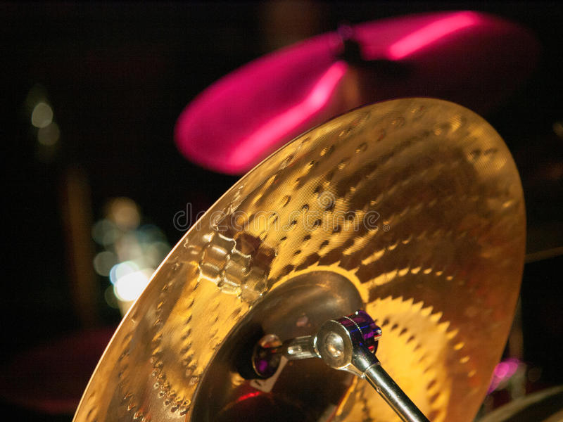 Back of Drum Cymbal. Back of one gold drum cymbal and another cymbal lit up with pink lights stock photo