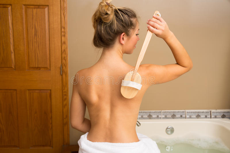 Back Dry Brush. Young woman sitting on edge of bath holding wooden-handle dry brush to her bare back stock image