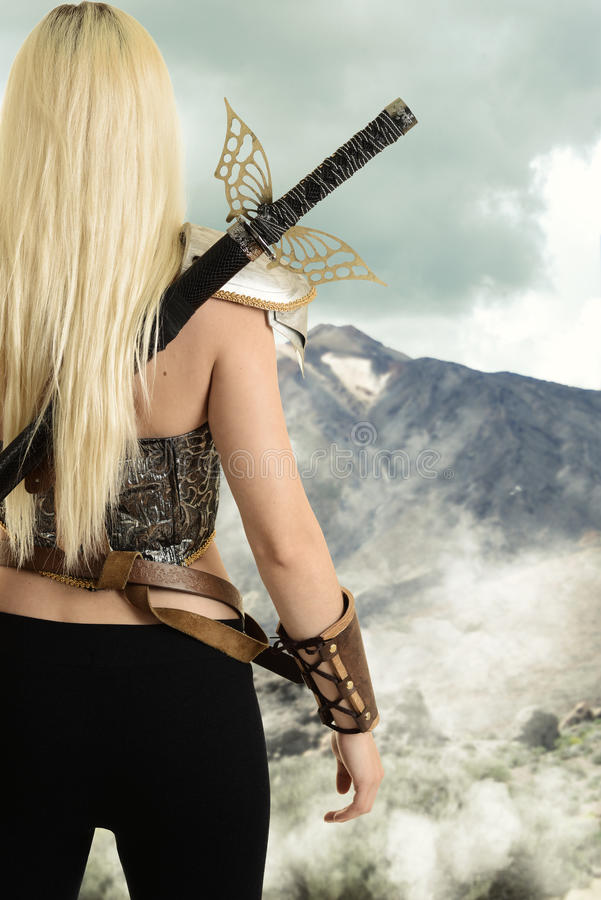 Back of female warrior looking at mountain stock photos