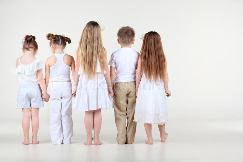 Back of four little girls and boy standing and holding hands stock images
