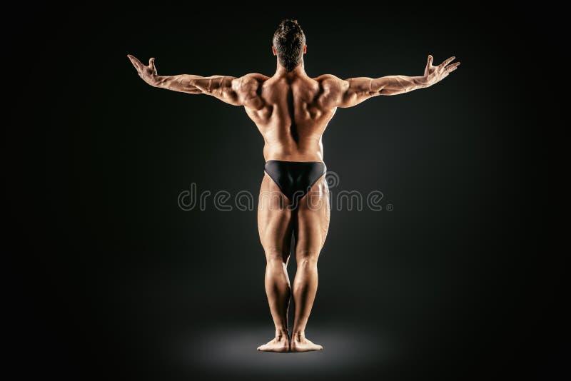 Back full length. Beautiful muscular man bodybuilder posing back over dark background. Full length royalty free stock photo