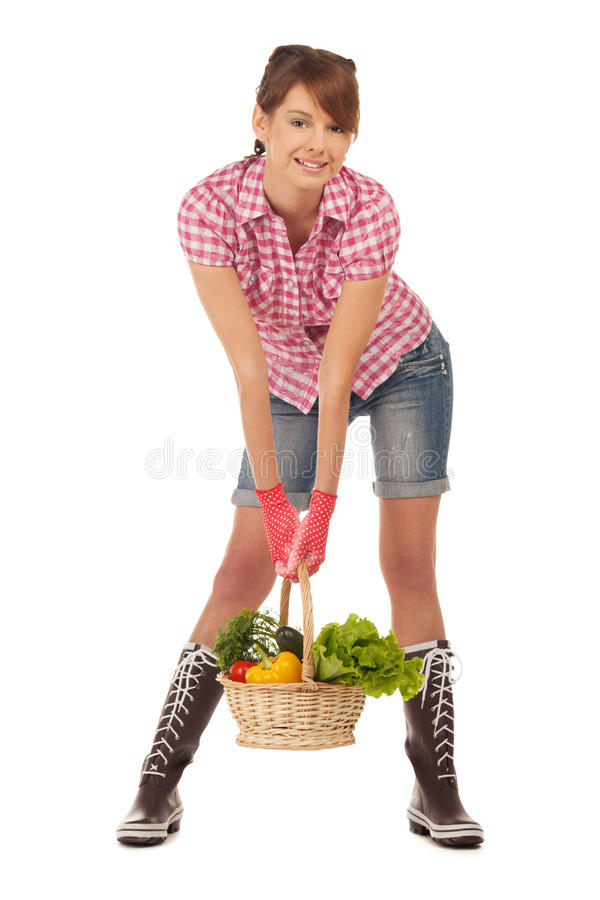 Back from the garden. Young girl with garden gifts in a basket royalty free stock photography