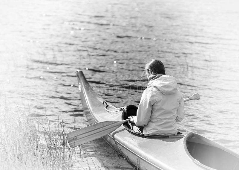 Back of the girl in boat with oar sepia backgorund royalty free stock photo