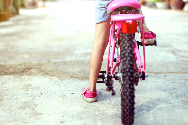 Back of girl start cycling. Asean child learn to ride bicycle herself royalty free stock images