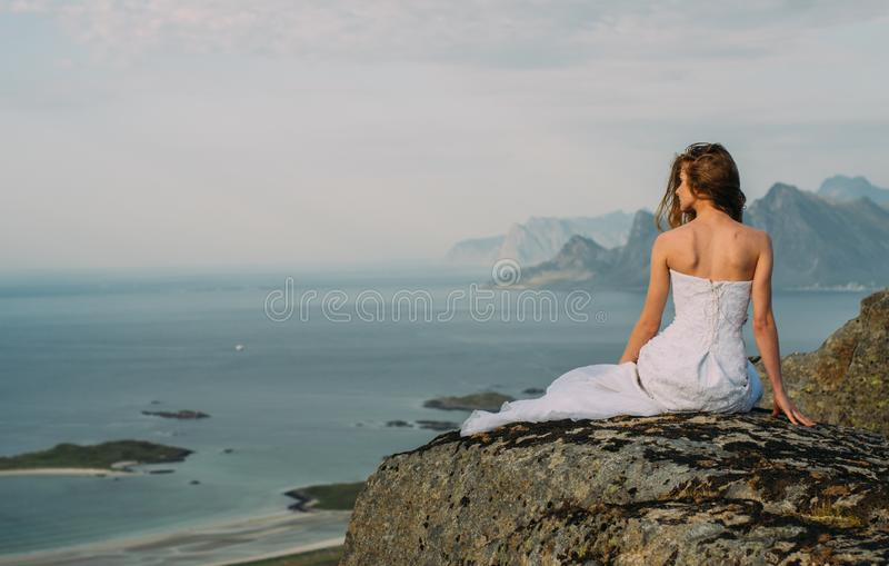 Back of girl in wedding dress sitting on rocks in mountains and looking to fjord royalty free stock photo