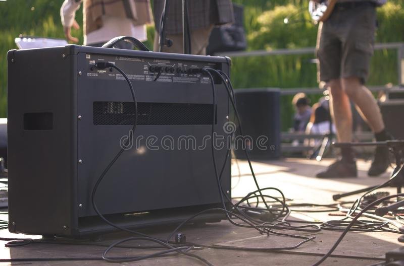 Back of a guitar amp on the stage. Of the concert with musicians playing on the background royalty free stock images
