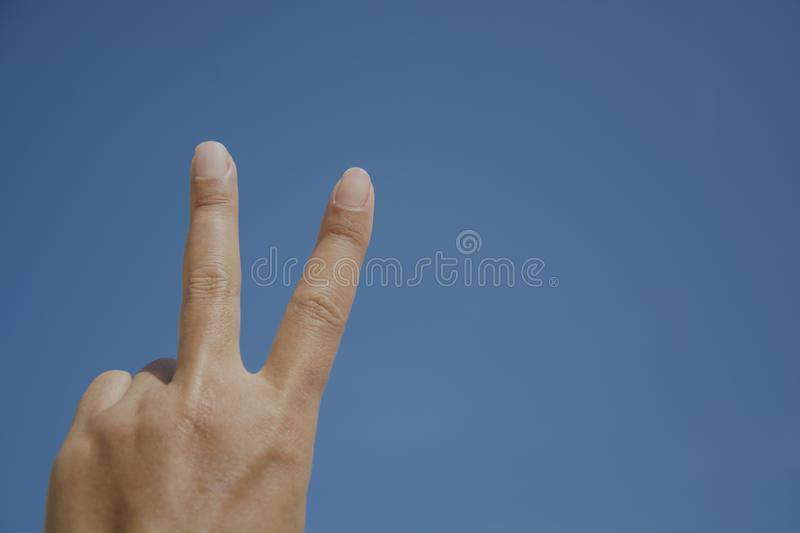 The back of hand show the victory sign against of woman hand with blue sky, finger shape stock photo
