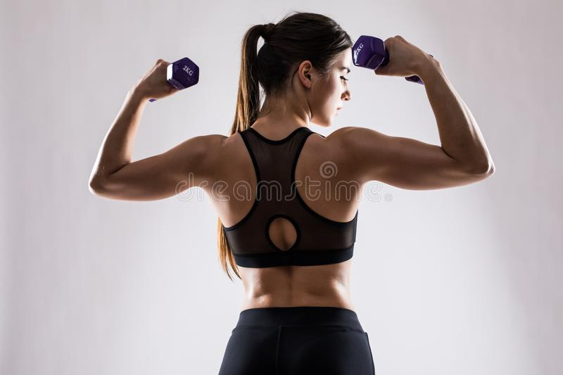 Back and hands of a young brunette sporty muscular woman working out with two metal dumbbells, isolated against white background royalty free stock photo