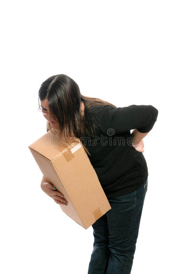 Back Injury. A teenage girl injured her back while trying to lift a box, isolated against a white background stock photography