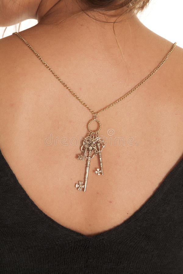 Back key necklace. A close up of a woman's back wearing a necklace with key charms royalty free stock images