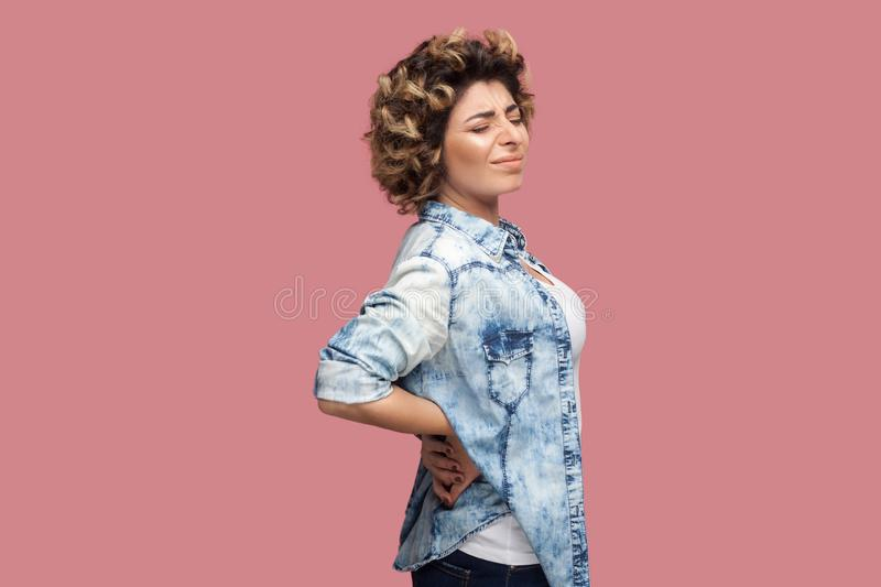 Back, kidney or spine pain. Profile side view portrait of sad young woman with curly hairstyle in casual blue shirt standing and royalty free stock image