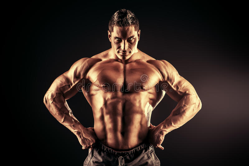 Back light. Handsome muscular bodybuilder posing over black background royalty free stock photos