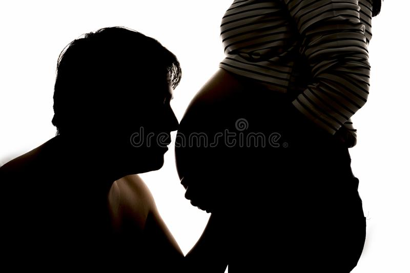 Back light of a pregnant woman. Silhouette of young pregnant female and dad male on white background. Backlit silhouette. Father a. Nd mother enjoying stock images