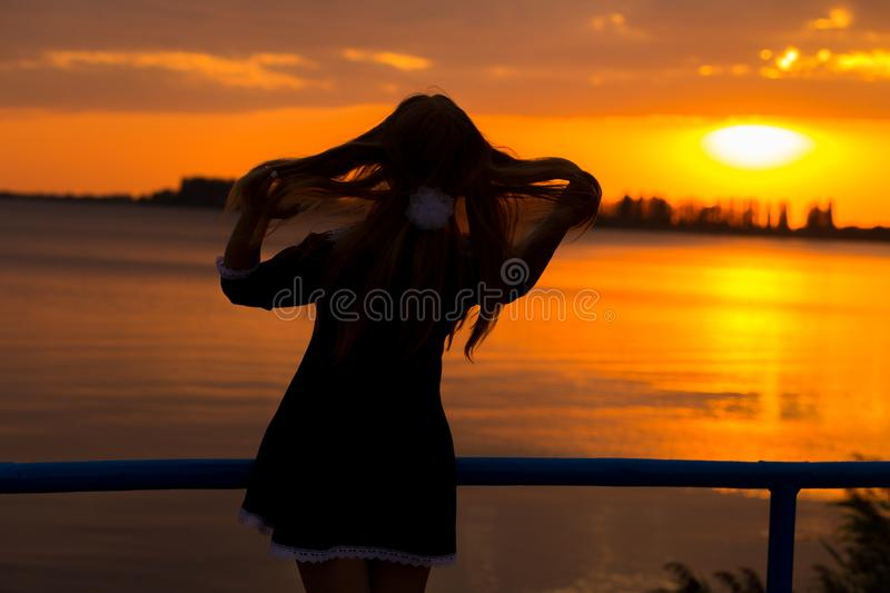 Back light of a woman silhouette breathing deep fresh air at warm sunrise in front of sun. female lightness and airin. E view of back light of a woman silhouette stock photos