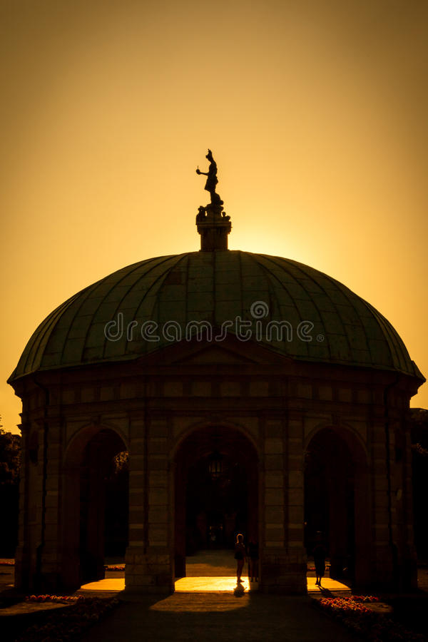 Back lit Hofgarten building with statue at top. Back lit dome on building with statue at top in Hofgarten at Munich, Germany during sunset or sunrise under royalty free stock image