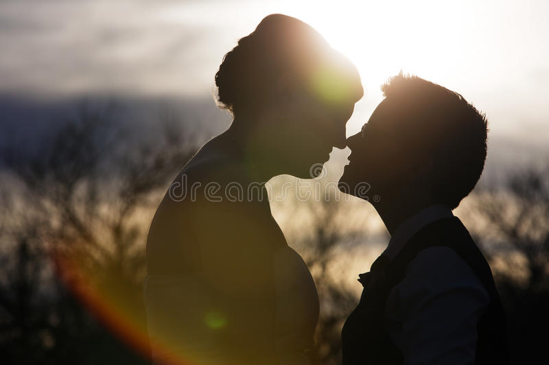 Back Lit Loving Couple. Silhouette of same sex couple close together outdoors stock photography