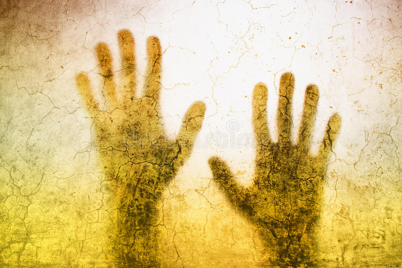 Back lit silhouette of trapped person hands behind matte glass. Useful as illustrative image for human trafficking, prostitution, imprisonment, mental illness stock photography