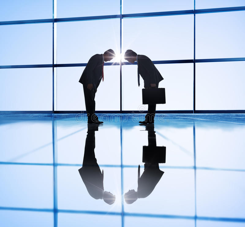 Back Lit of Two businessmen Bowing.  royalty free stock photos