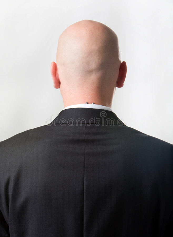 Back of man. Rear view of bald man wearing suit over white background royalty free stock images