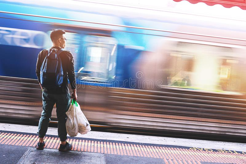 Back of a man waiting for the train under the sunlight at station in Melbourne, Australia royalty free stock photography