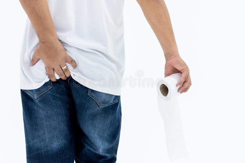 The back of a man Which uses left hand Hold ass area And hold a tissue. Whit right hand, concept to people have diarrhea Want to go to bathroom for excretion royalty free stock images