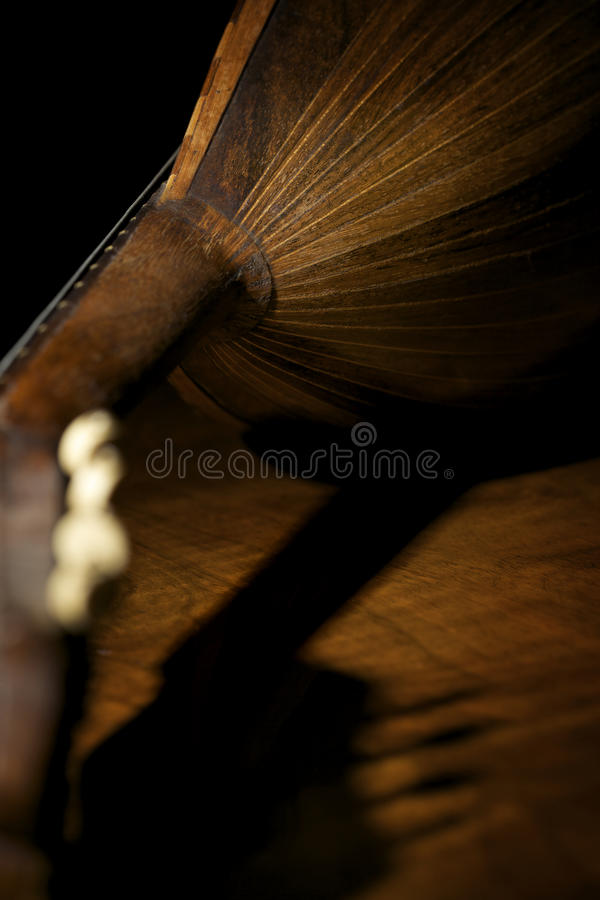 Back of mandolin. Closeup of backside of old mandolin lying on wooden board and black background royalty free stock photo