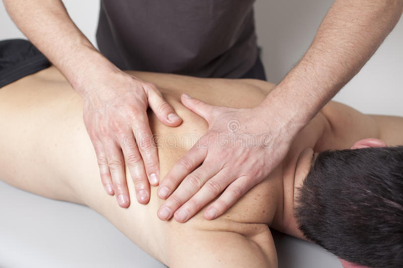 Back massage. Massagist giving back massage to patient royalty free stock photos