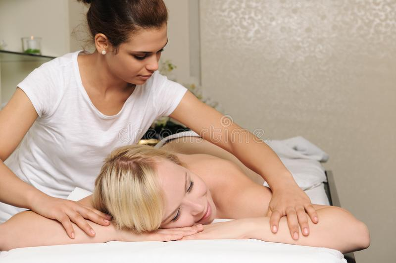 Back massage. Blond women getting massage in spa salon stock image