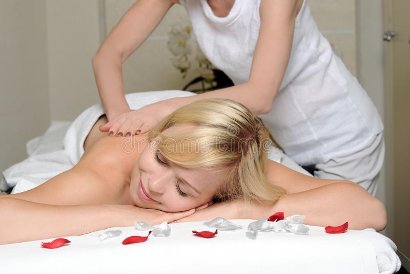 Back massage. Blond women getting massage in spa salon stock photo