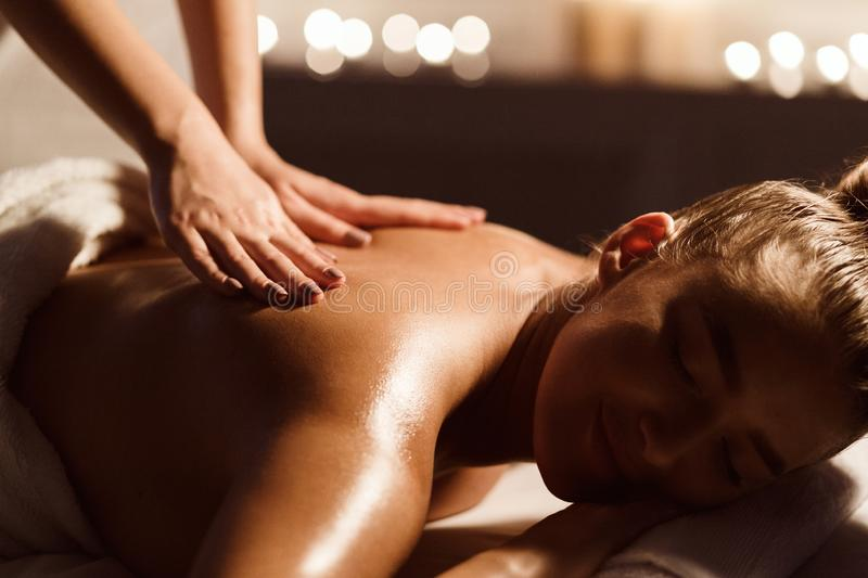 Back Massage. Woman Relaxing In Atmospheric Spa Salon. With Candles On Background stock images
