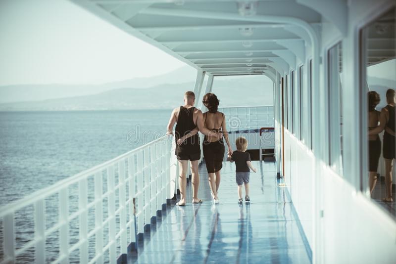 Back of mother, son and father dressed in swimsuits walking on deck of ship. stock photos