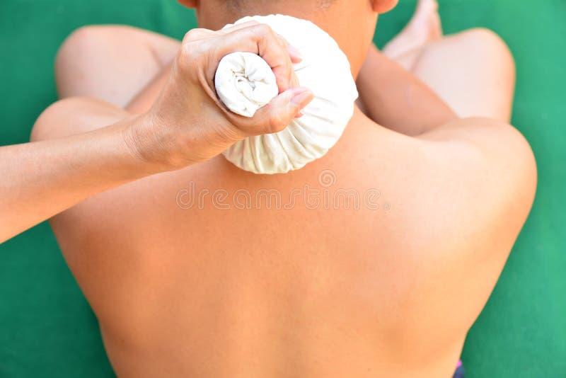Back neck massage. Massage therapist massaging back neck of a ma. Le royalty free stock image