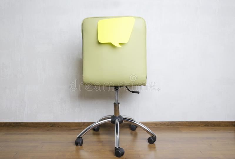 Back of office chair and paper speech bubble on it.What are employees thinking about during the work? royalty free stock image