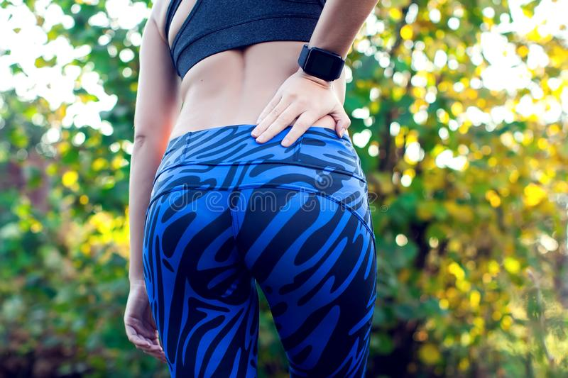 Back Pain. Athletic fitness woman rubbing the muscles of her low royalty free stock photos