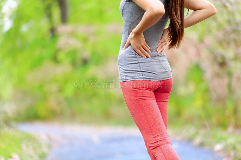 Back pain - Athletic running woman with back injury. Back pain. Athletic running woman with back injury in sportswear rubbing touching lower back muscles stock photo
