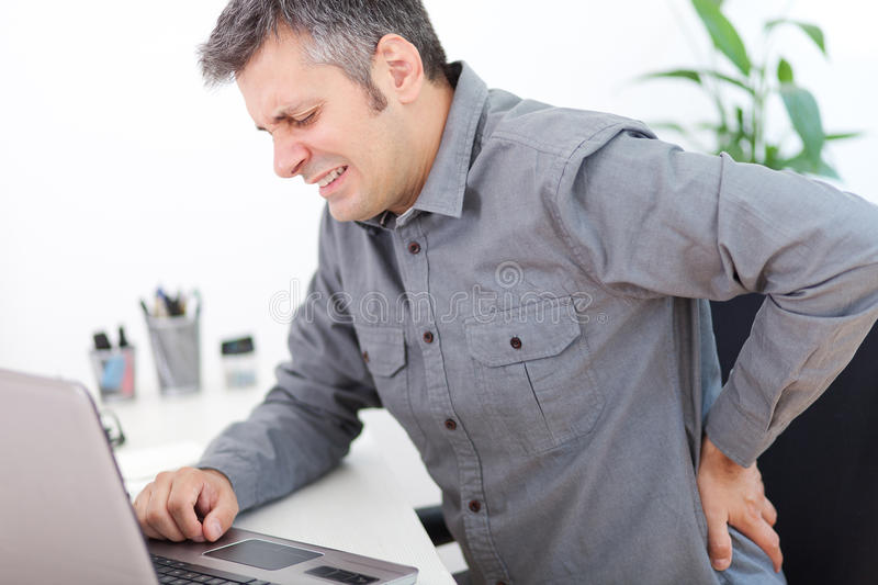 Back pain. Image of a young man having a back pain while sitting at the working desk stock images