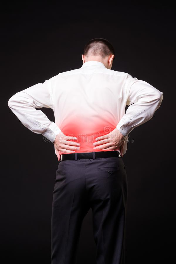 Back pain, kidney inflammation, ache in man`s body. On black background with red dot royalty free stock images