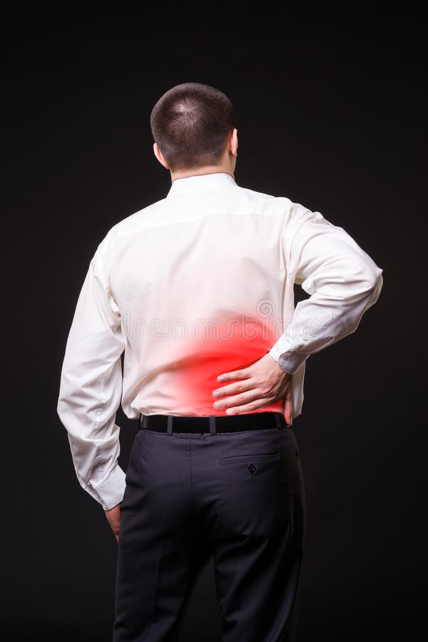 Back pain, kidney inflammation, ache in man`s body. Close-up on black background with red dot stock photo